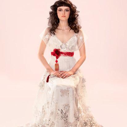 chica sentada en una silla usando un vestido de color blanco con una cinta color roja