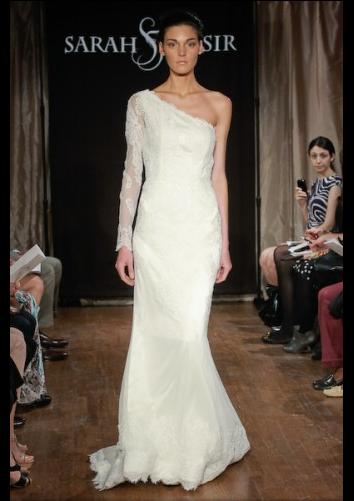 mujer caminando por la pasarela de un desfile de modas portando un vestido de color blanco con una manga de lado derecho