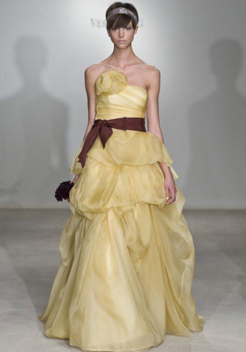 chica desfilando en una pasarela de modas con un vestido color amarillo con café