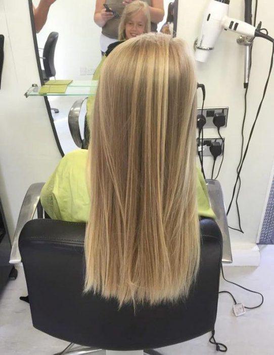 Niña con el cabello largo y rubio sentada en una silla esperando que su estilista corte su cabello