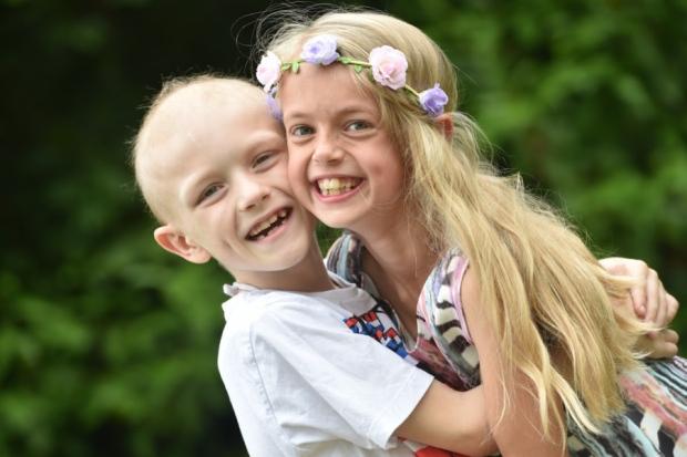 NIño con cáncer abrazado a una niña que tiene el cabello largo y rubio con una corona de flores