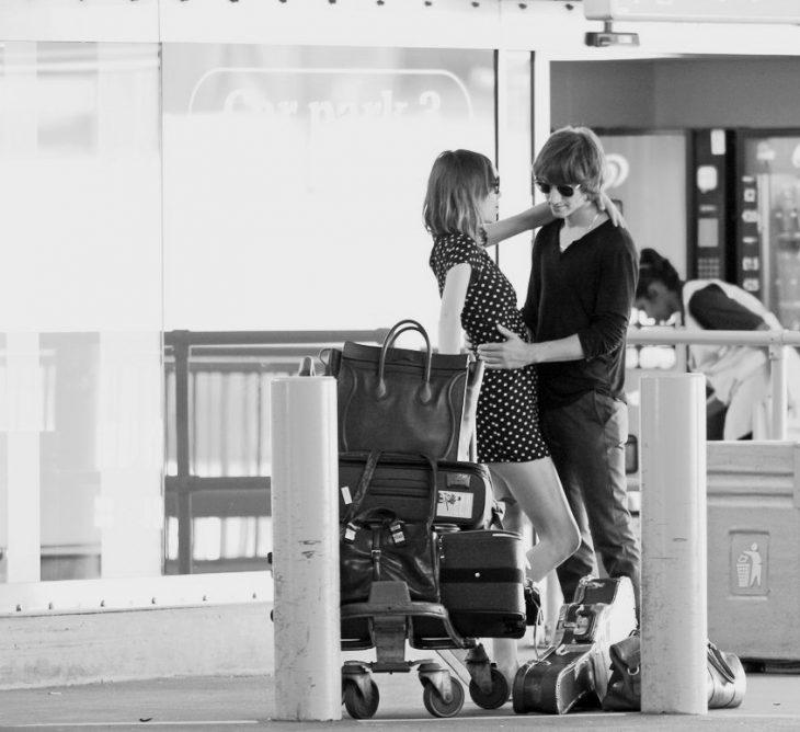Pareja de novios en el aeropuerto abrazados