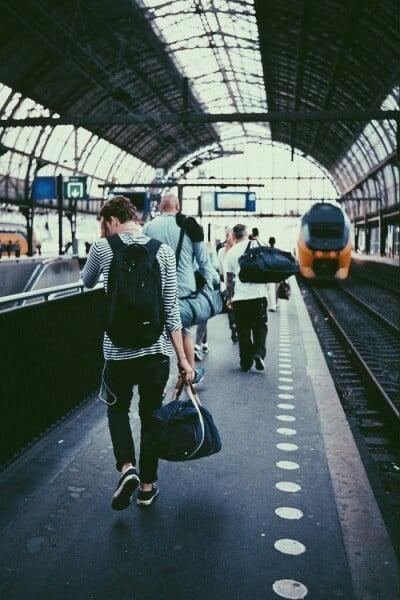 Chico con una maleta en sus manos y una mochila mientras camina por la terminal del tren