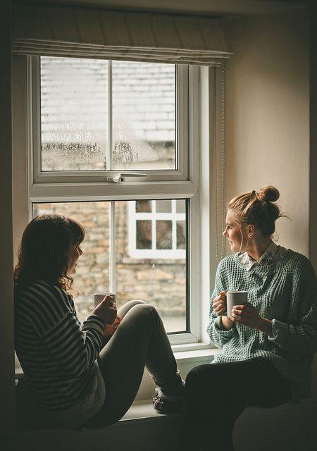 Chicas frente a una ventana conversando