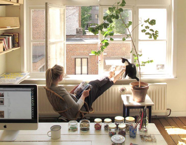 Chica sentada en una silla frente a una ventana leyendo una revista