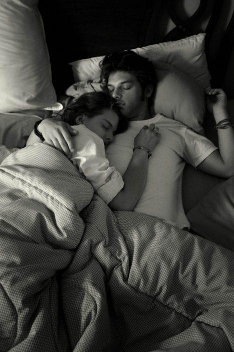 Pareja de novios dormidos en una cama