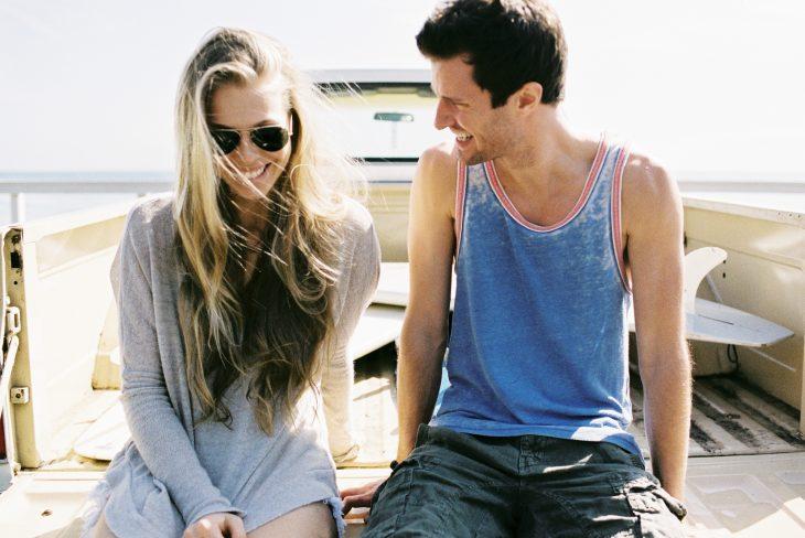 Chica sonriendo junto a un chico mientras están sentados en una barca