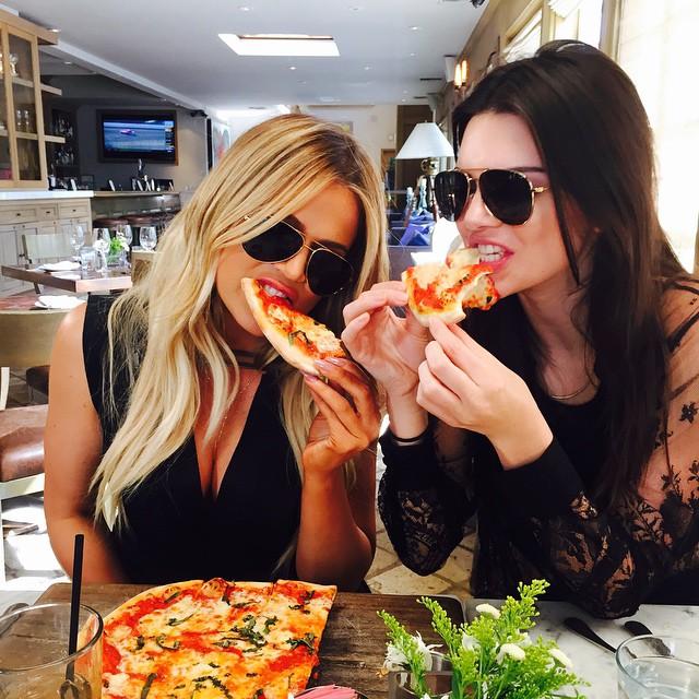 Chicas comiendo pizza en un restaurante