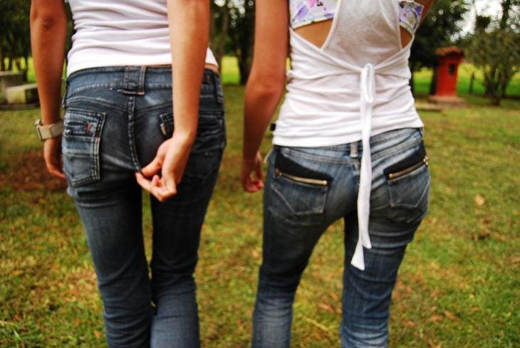 Chicas caminando mientras una de ellas se toca el trasero