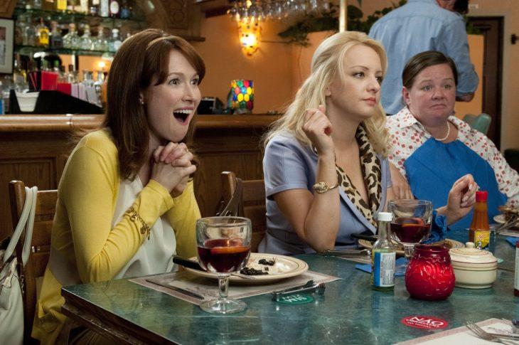 Chicas en una reunión de comida con la cara de aburrimiento