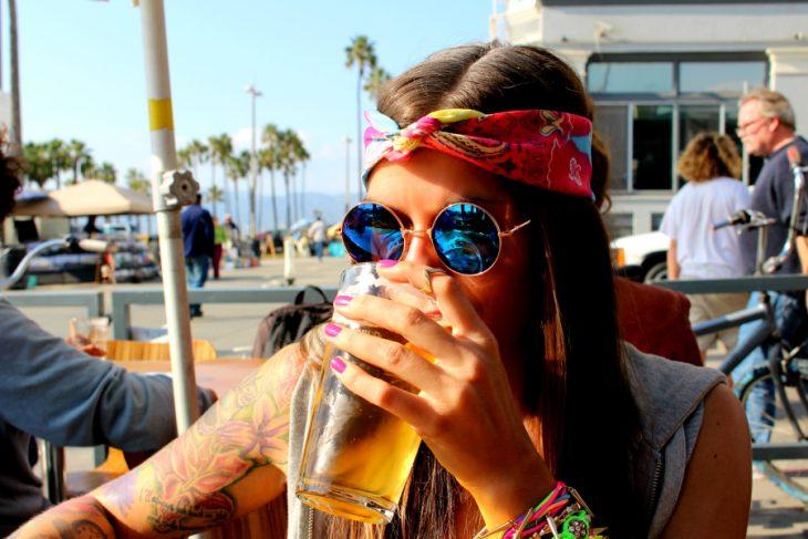 Chica bebiendo cerveza vestida como hippie