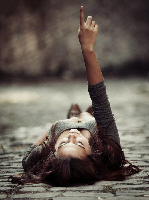 Chica mirando y señalando al cielo