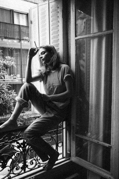 Chica en una ventana pensando y fumando