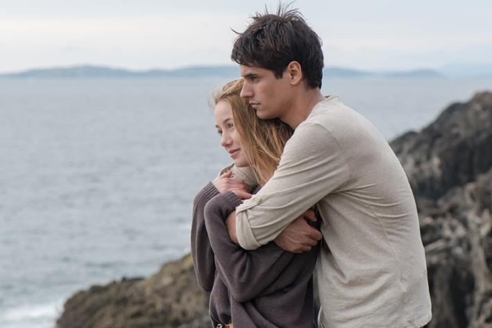 Pareja de novios abrazados parados en una roca viendo hacia el mar