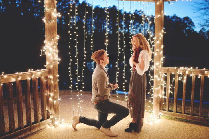 Chico proponiendole matrimonio a una chica en un kiosco con luces