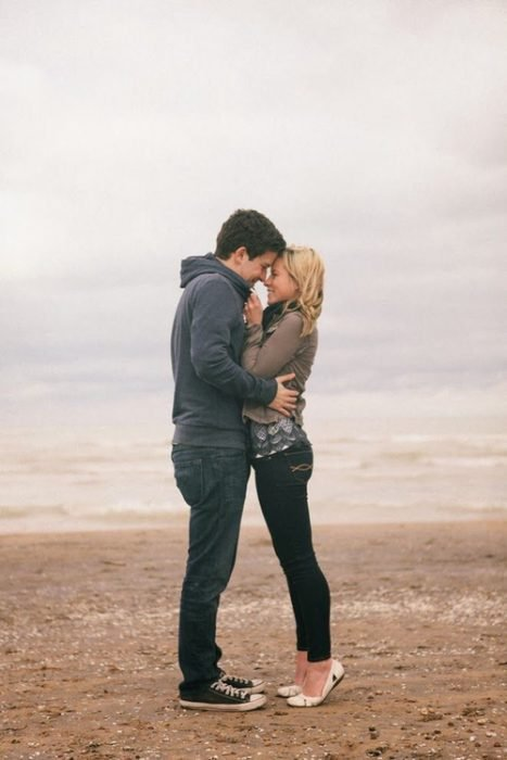 Pareja de novios abrazados mientras estan parados en una playa viendo el mar