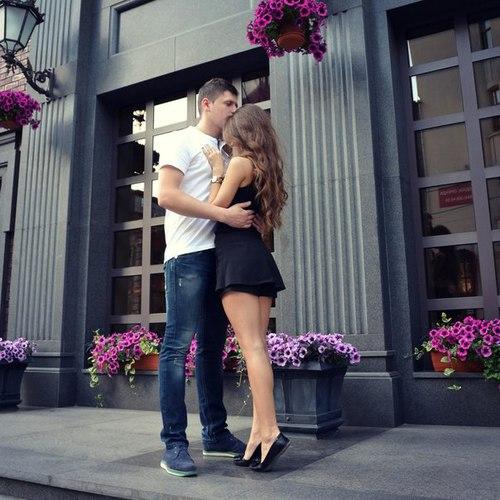Chico besando la frente de una chica mientras están afuera de una tienda