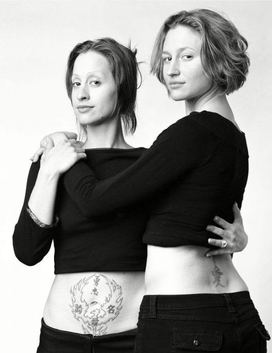 mujeres abrazadas con tatuajes que parecen gemelas