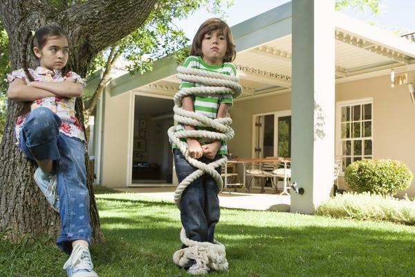 Niña amarrando con una cuerda a un niño que está en el jardín de su casa