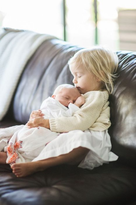 Niña besando en la frente a un bebé mientras ambos están senados en un sofá