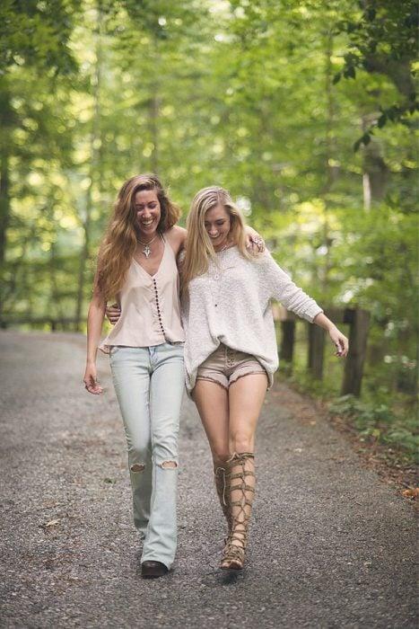 Chicas abraadas caminando por la carretera rodeadas de árboles mientras están abrazadas
