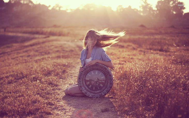 Chica sosteniendo un reloj grande mientras esta sentada en la hierba