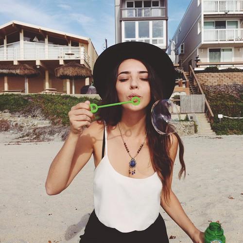 Chica haciendo bombas de jabón en la playa