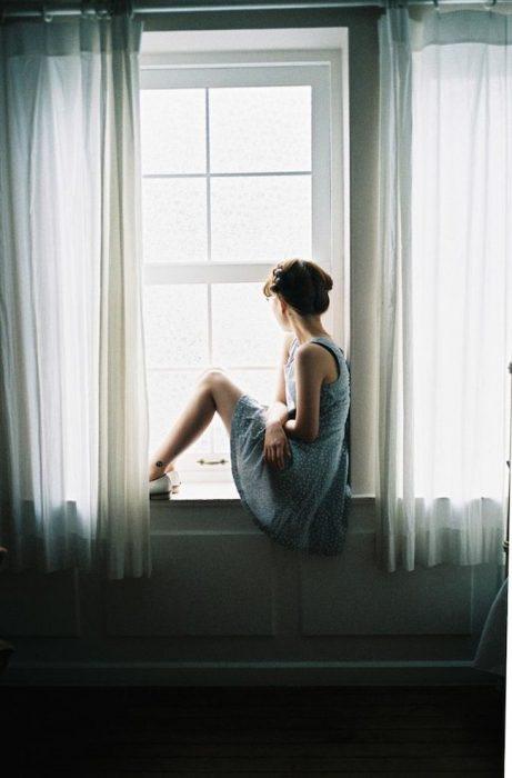 Chica sentada observando por la ventana