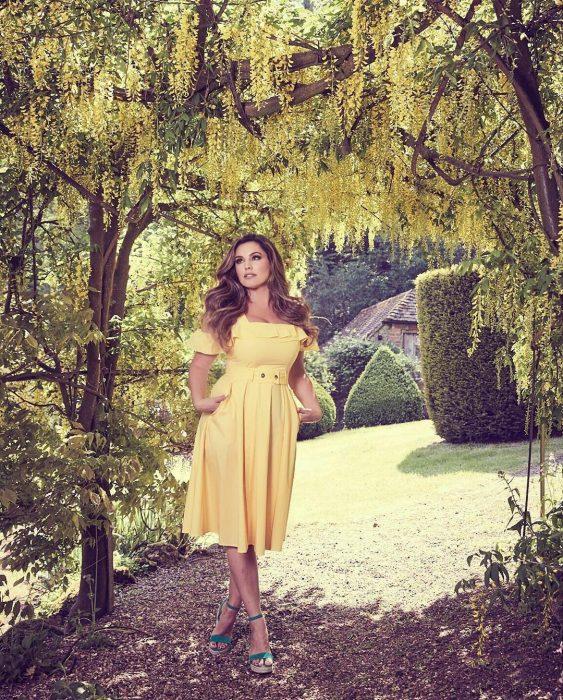 Chica usando un vestido amarillo mientras está en un campo bajo un árbol
