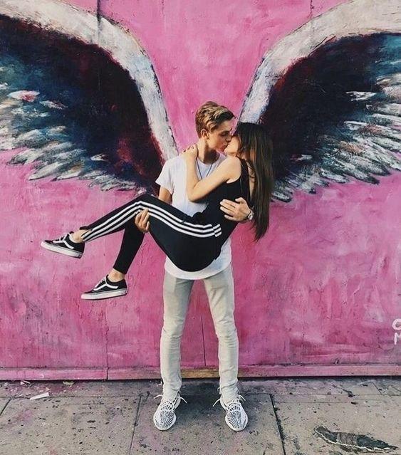 Pareja de novios tomandose una foto con unas alas en una pared