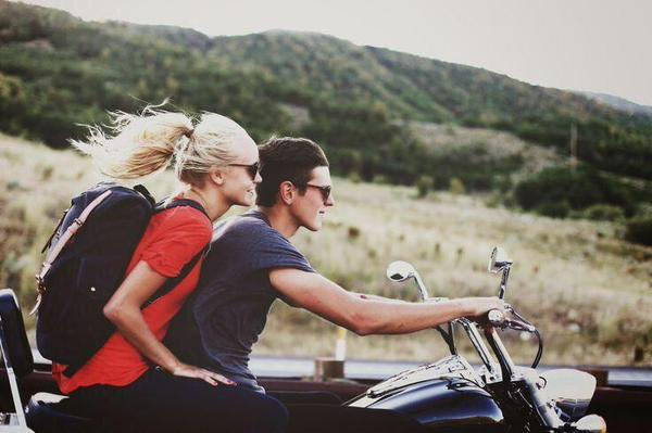 Pareja de novios viajando en una motocicleta por la carretera