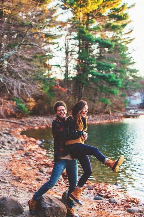 Pareja de novios disfrutando de una puesta de sol en un lago
