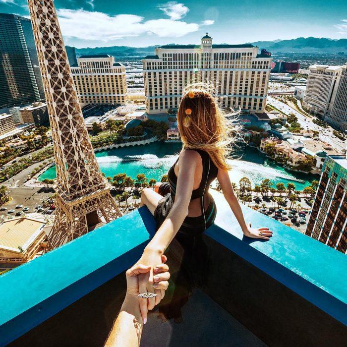 Pareja Follow me to chica sentada en una balcón viendo la ciudad e las vegas