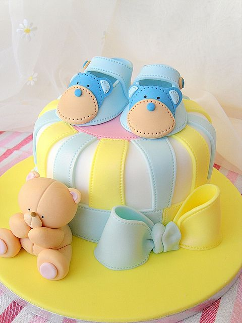 pastel para baby shower en color amarillo con azul y decoraciones de fondant de zapatitos y osos