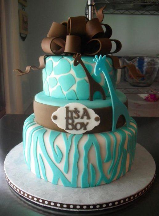 Pastel de color azul con un moño café en la cima y jirafas en la segunda torta