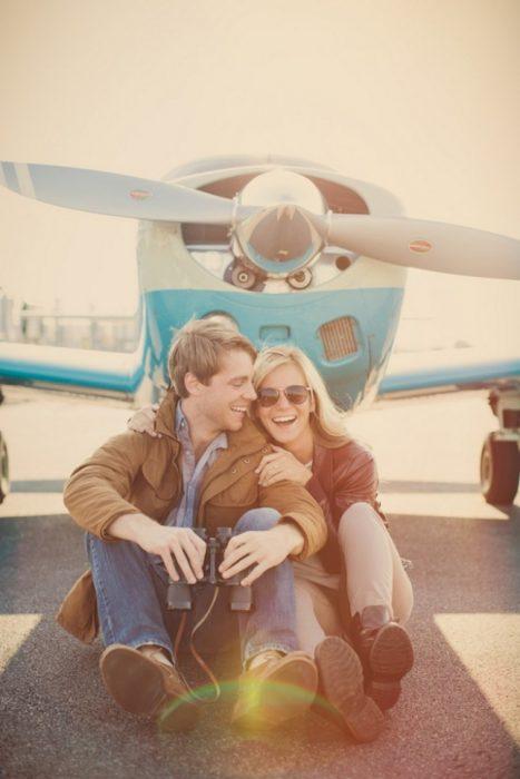 Pareja sentada en la pista de aterrizaje frente a un avión