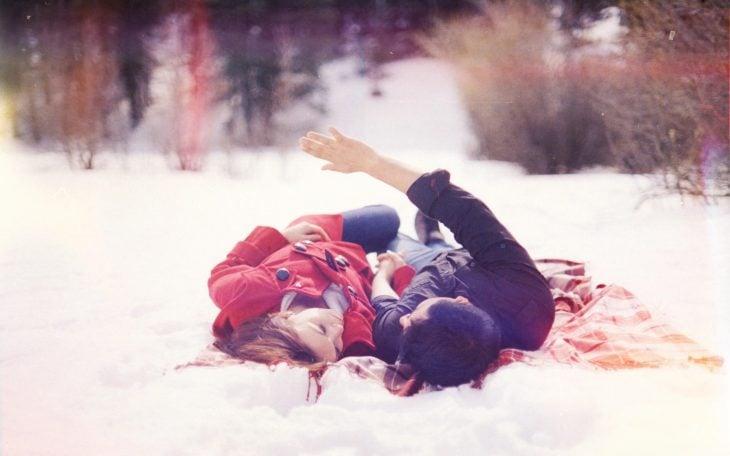 Pareja de novios acostados en la nieve