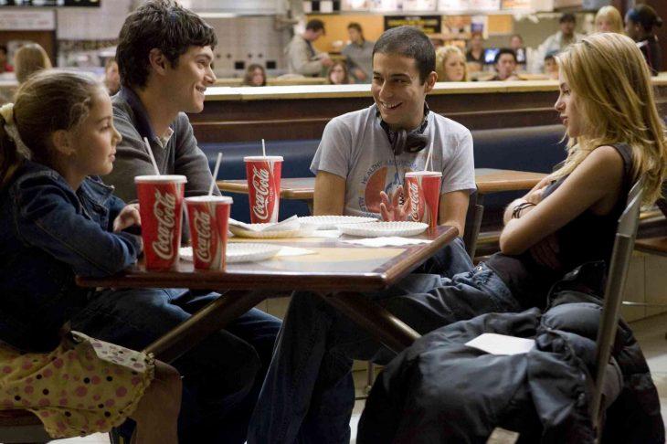 chicos en una mesa con cocas conversando