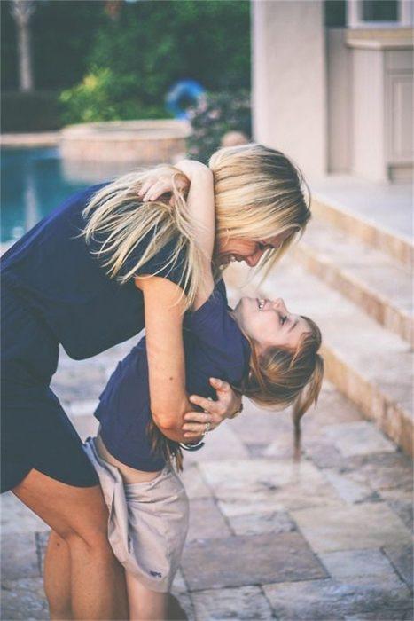 Chica abrazando a una niña pequeña
