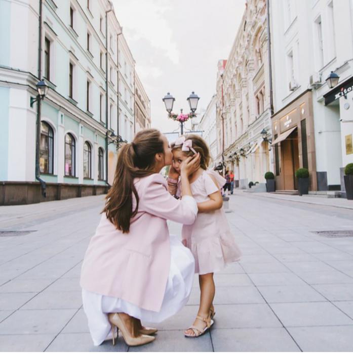 Chica besando la frente de una niña