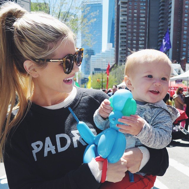 Chica cargando a un bebé y sonriendo
