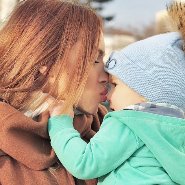 Chica besando la nariz de un bebé