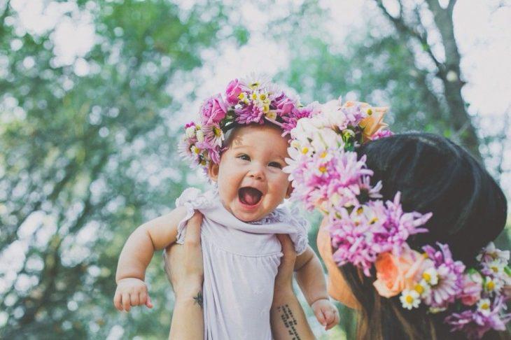 Chica cargando a una bebé con una corona de flores