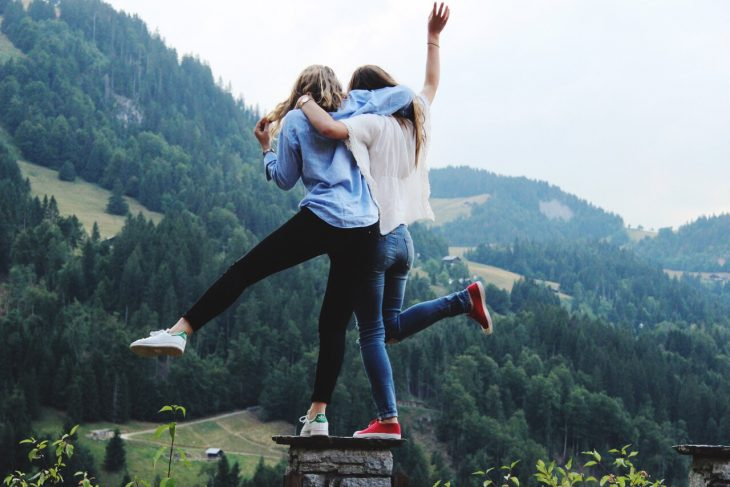 Chicas abrazadas y levantando un pie