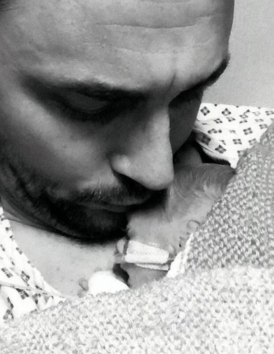 Padre sosteniendo a su bebe que pesa 600 gramos contra su pecho y besándolo en la frente