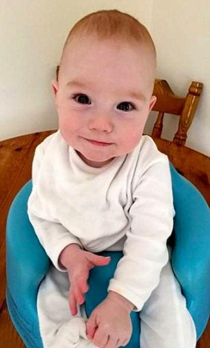 Bebé sentado en una silla mientras está sonriendo