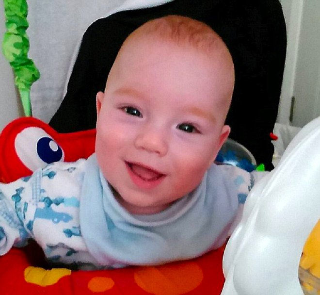 Bebé en una andadera sonriendo mientras le toman una fotografía