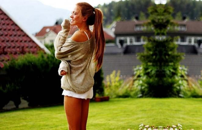 Chica parada sobre el pasto usando shorts sudadera y una cola de caballo