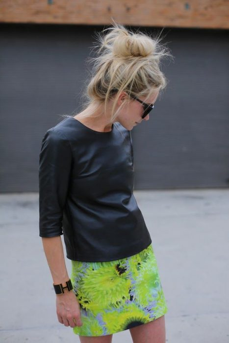 Chica usando una falda verde y una blusa negra de cuero con gafas de sol y un chongo