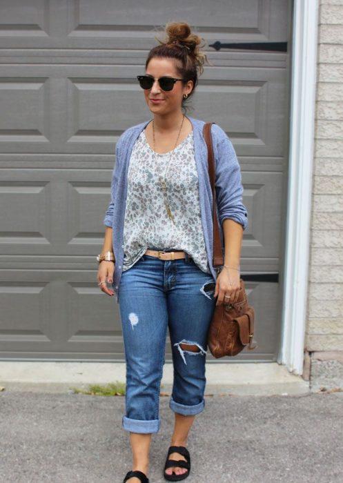 Chica usando pantalones rasgados camisa suéter morado y bolsa